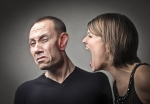 Angry woman screaming against her husband with his face deformed